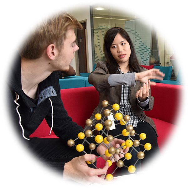 Two materials chemists discuss a 3-dimensional model of a molecule